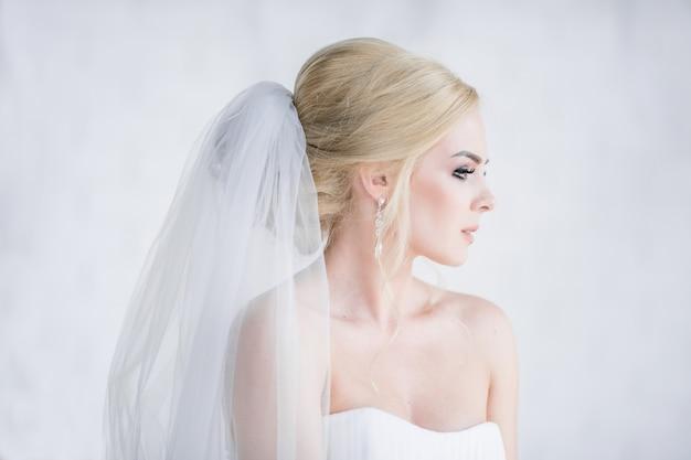 Ritratto di splendida bionda sposa in abito con le spalle nude
