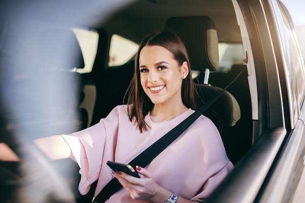 Ritratto di splendida bruna con grande sorriso a trentadue denti alla guida di auto, utilizzando smart phone e guardando la fotocamera.