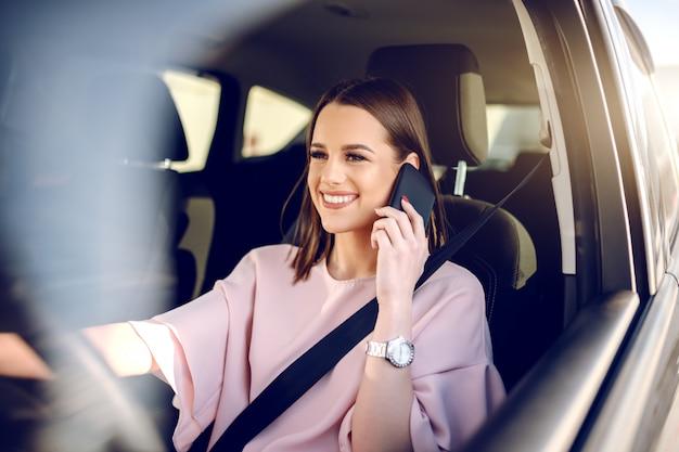 Ritratto di splendida bruna con un grande sorriso a trentadue denti alla guida di auto e utilizzando smart phone.