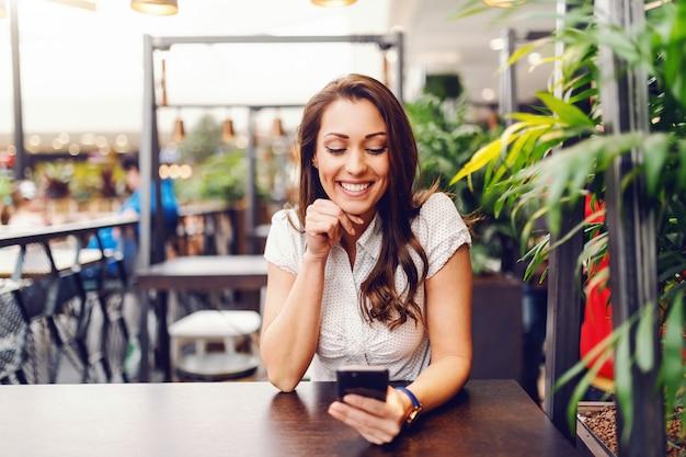 Ritratto di splendida brunetta caucasica in camicia utilizzando smart phone e seduto al bar.