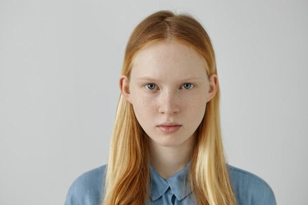 Ritratto di splendida ragazza europea con lentiggini e occhi azzurri che indossa i suoi capelli biondi sciolti nascosti dietro le orecchie