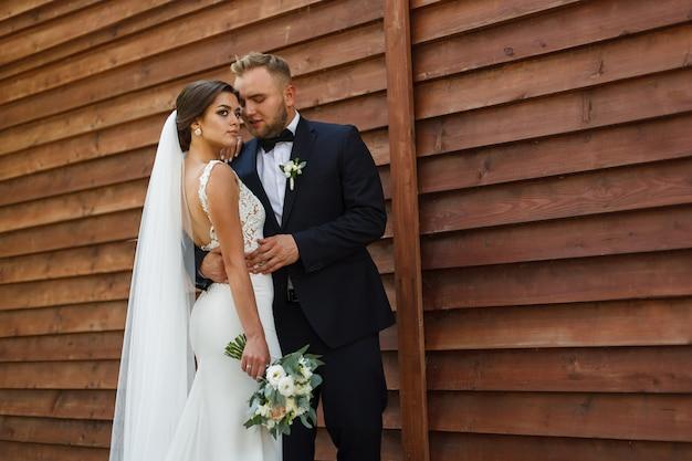 Ritratto di spose sorridenti felici su un fondo di legno. nozze . sposa e sposo emozionali al giorno delle nozze all'aperto in primavera. giovani sposi godendo momenti romantici all'esterno.