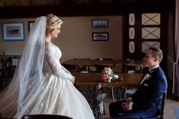 Ritratto di sposi felici al coperto. sposi sorridenti emotivi al giorno del matrimonio. gli sposi si guardano delicatamente negli occhi. felice coppia appena sposata