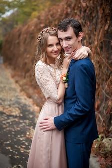 Ritratto di sposi felici in natura autunnale. sposi felici abbracciando e baciando.