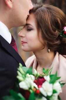 Ritratto di sposi felici in natura autunnale. sposi felici abbracciando e baciando