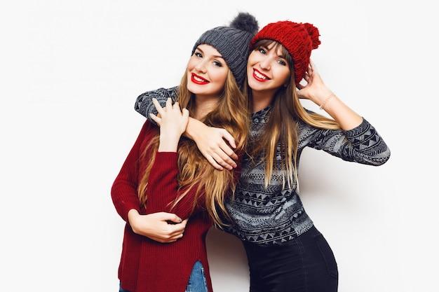 Ritratto di stile di vita al coperto di due donne abbastanza felici, migliori amiche in cappelli lavorati a maglia carini e maglioni accoglienti divertendosi