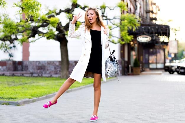 Ritratto di stile di vita all'aperto della donna elegante che cammina nel centro della città dell'europa, divertendosi e sorridendo,