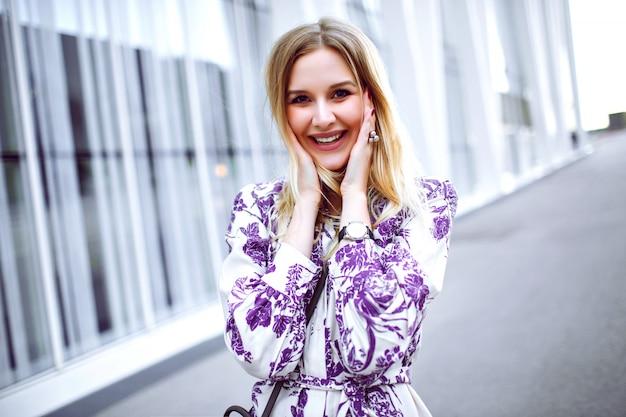 Ritratto di stile di vita all'aperto di donna bionda sorridente uscita che indossa un abito floreale alla moda elegante e guardando a porte chiuse, primavera estate.