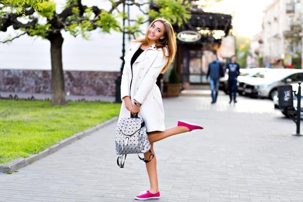 Ritratto di stile di vita all'aperto di donna elegante che cammina nel centro di europa, divertendosi e sorridendo, indossando cappotto beige e abito glamour, umore hipster, vacanza in viaggio, tempo di autunno.