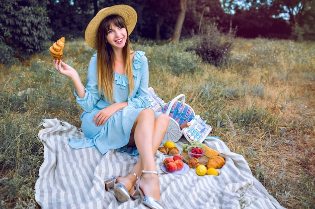 Ritratto di stile di vita all'aperto di donna elegante magnifica abbastanza elegante che indossa abito femminile vintage blu e cappello di paglia
