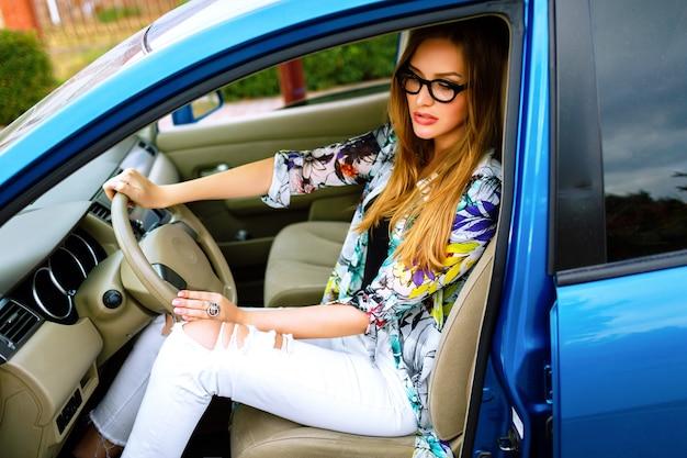 Ritratto di stile di vita all'aperto di giovane viaggiatore hipster ragazza alla guida di auto, fermandosi e rilassarsi, bella giornata, concetto di gioia di viaggio. luminoso outfit street style alla moda.