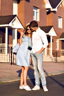 Ritratto di stile di vita all'aperto di una coppia abbastanza giovane in un appuntamento romantico divertendosi insieme, baci e abbracci, in posa per strada, viaggiare insieme, ritratto di famiglia.