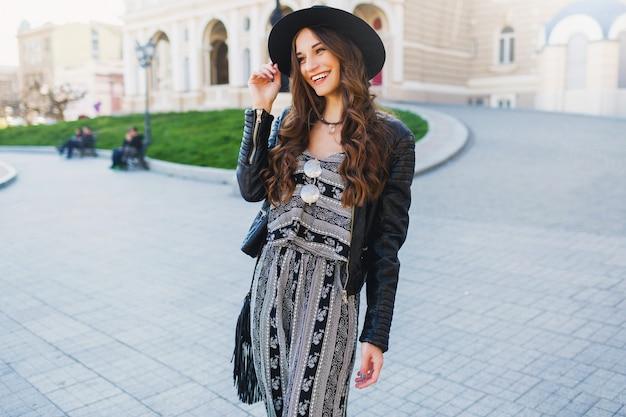 Ritratto di stile di vita della donna abbastanza allegra godendo le vacanze nella vecchia città europea. look alla moda di strada. vestito primaverile alla moda.