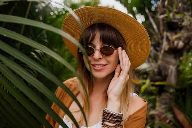 Ritratto di stile di vita della donna castana in cappello di paglia che posa sulle foglie di palma tropicale