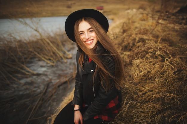 Ritratto di stile di vita della giovane donna in cappello nero che riposa in riva al lago in una bella e calda giornata d'autunno.