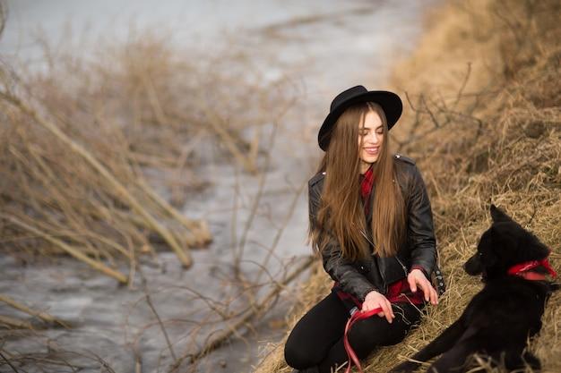 Ritratto di stile di vita della giovane donna in cappello nero con il suo cane