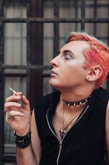 Ritratto di stile di vita della sigaretta fumatori uomo gay con espressione facciale soddisfatta