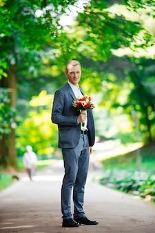 Ritratto di stile di vita dello sposo felice che posa per la macchina fotografica all'aperto sulla natura