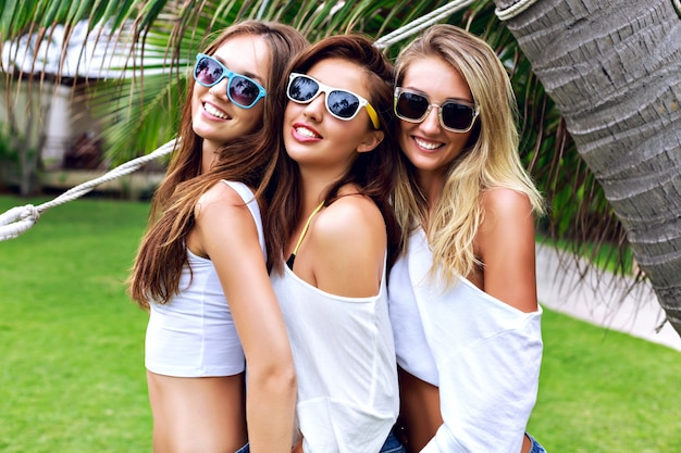 Ritratto di stile di vita di estate degli amici della donna abbastanza giovane dell'albero che si divertono insieme al bel giorno d'estate al paese tropicale, tre donne godono della loro vacanza, pronta per la festa