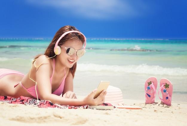 Ritratto di stile di vita di estate della giovane donna che si distende sulla spiaggia.