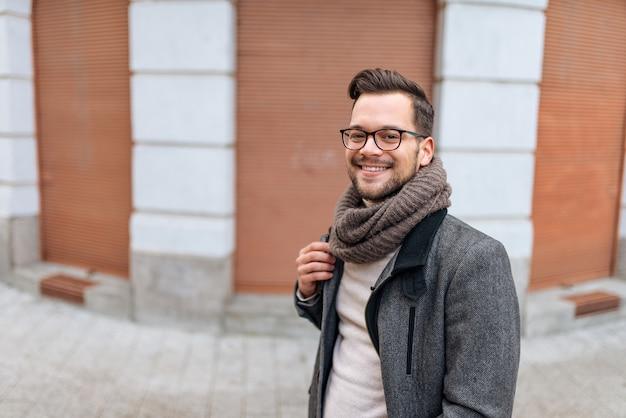 Ritratto di stile di vita di inverno dell'uomo sorridente con lo zaino che cammina nella città.