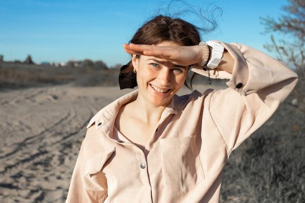 Ritratto di stile di vita di moda di giovane donna alla moda vestita in camicia ridendo, sorridente, in posa sulla spiaggia