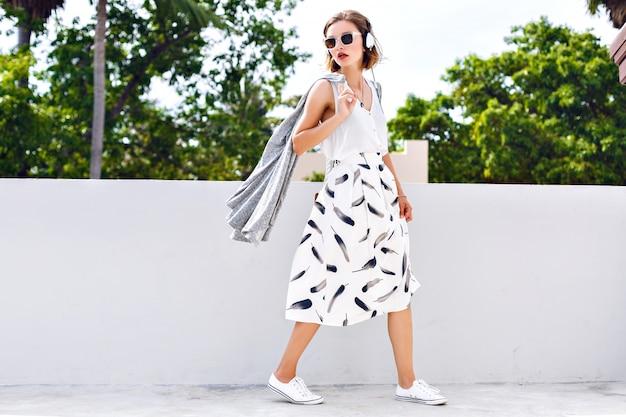 Ritratto di stile di vita di moda di giovane donna graziosa felice che salta e si diverte per strada in una bella giornata di sole estivo, ascoltando la musica preferita con gli auricolari, vestito vintage elegante, colori freschi e luminosi.
