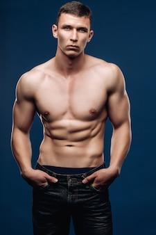 Ritratto di stile di vita di un modello maschile con un torso muscoloso guardando la telecamera, le mani nella tasca dei jeans, pantaloni in alto.