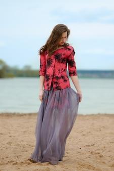 Ritratto di stile di vita di una giovane donna sulla spiaggia in gonna trasparente e giacca con stampe.