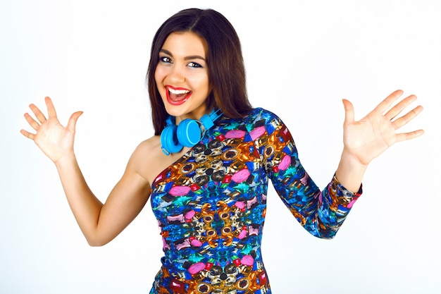 Ritratto di stile di vita divertente di bella donna in abito da festa elegante luminoso e grandi cuffie blu divertendosi, emozioni positive.