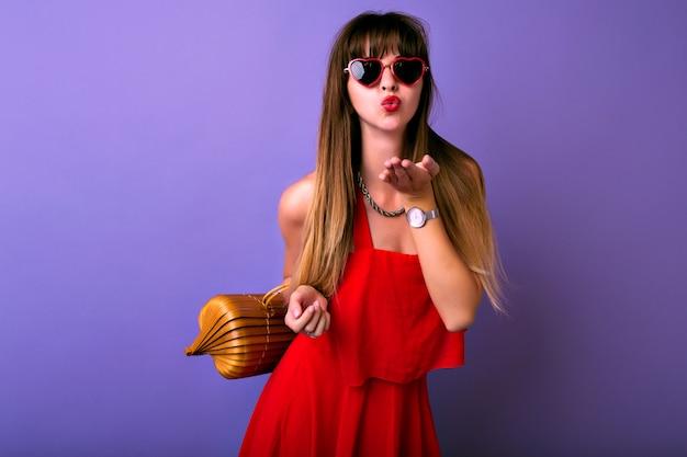 Ritratto di stile di vita in studio di donna alla moda piuttosto mora che indossa un vestito rosso elegante estivo, occhiali da sole herat, borsa di legno, che ti invia un bacio d'aria.
