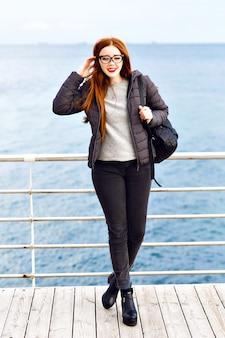 Ritratto di stile di vita invernale di donna allo zenzero piuttosto hipster che cammina in riva al mare, vestito elegante nero totale, tempo piovoso freddo, zaino, stivali di pelle, solitario.