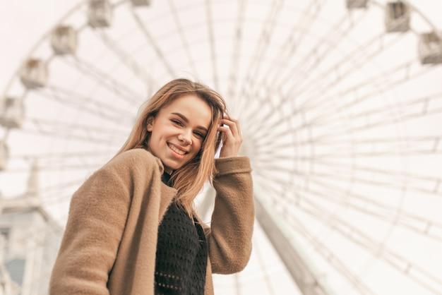 Ritratto di strada di una ragazza felice che indossa un cappotto in piedi nella strada della città sullo sfondo della ruota panoramica, guardando a porte chiuse e sorridente