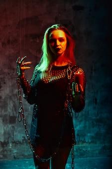 Ritratto di strega con il trucco di halloween con catene
