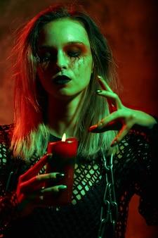 Ritratto di strega con il trucco di halloween con una candela