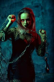 Ritratto di strega con il trucco di halloween con una catena