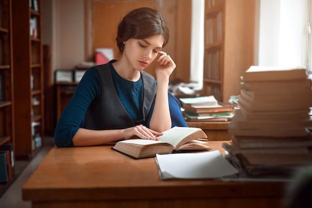 Ritratto di studente intelligente nella biblioteca universitaria.