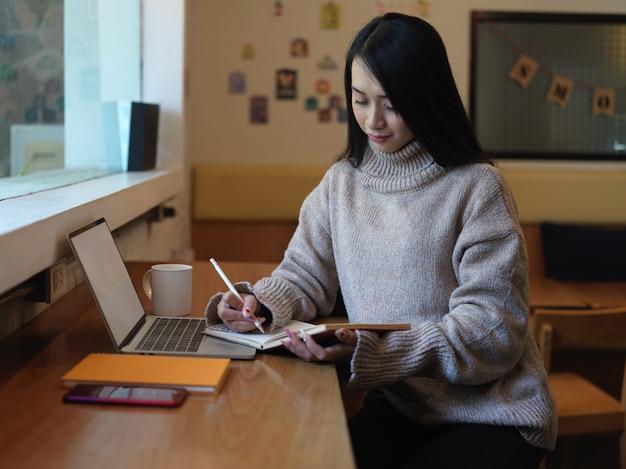 Ritratto di studentessa di college femminile che fa i compiti con cancelleria e laptop sul bancone della caffetteria