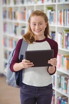 Ritratto di studentessa felice che tiene compressa digitale in libreria