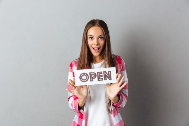 Ritratto di stupito giovane donna bruna con cartello aperto