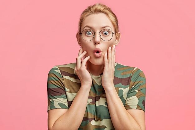 Ritratto di stupito modello femminile dagli occhi blu stupito in maglietta casual, posa da solo su sfondo rosa, esprime shock e sorpresa, isolato su rosa