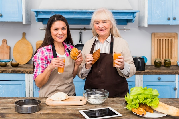 Ritratto di sua madre in piedi con la sua giovane figlia in possesso di croissant e succo al forno