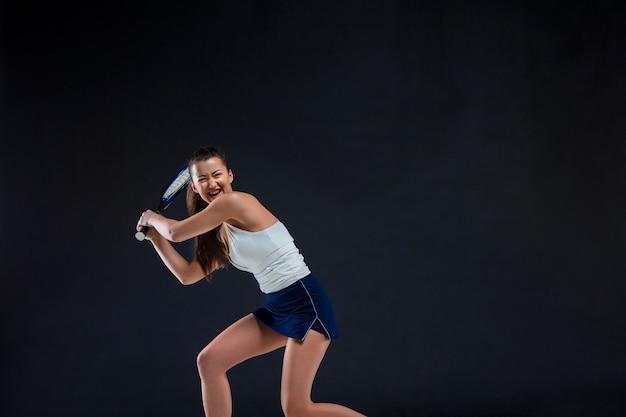 Ritratto di tennis bella ragazza con una racchetta sulla parete scura