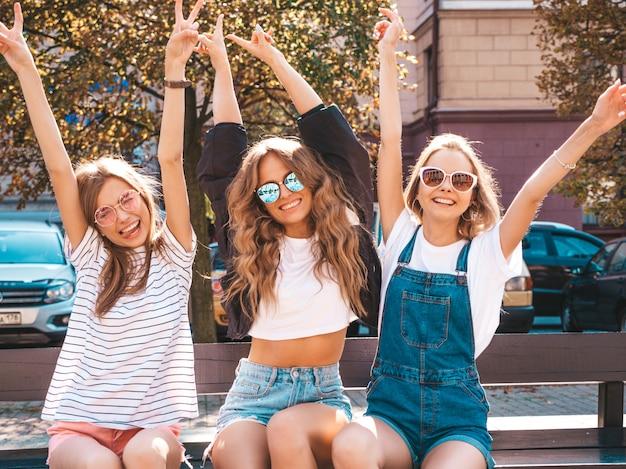Ritratto di tre giovani belle ragazze sorridenti dei pantaloni a vita bassa in vestiti estivi d'avanguardia donne spensierate sexy che si siedono sul banco nella via modelli modulari divertendosi in occhiali da sole mani alzanti