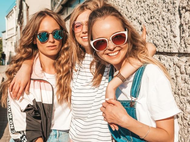 Ritratto di tre giovani belle ragazze sorridenti hipster in abiti estivi alla moda. donne spensierate sexy che posano nella strada vicino alla parete. modelli positivi che si divertono in occhiali da sole