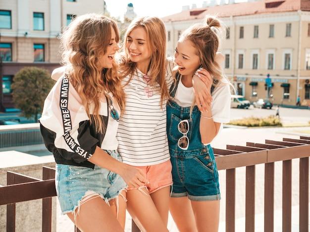Ritratto di tre giovani belle ragazze sorridenti hipster in abiti estivi alla moda. donne spensierate sexy che posano per strada. divertimento dei modelli positivi. comunicare e discutere qualcosa