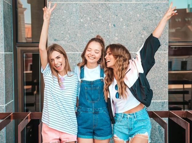 Ritratto di tre giovani belle ragazze sorridenti hipster in abiti estivi alla moda. donne spensierate sexy che posano per strada. divertimento dei modelli positivi. mani alzanti