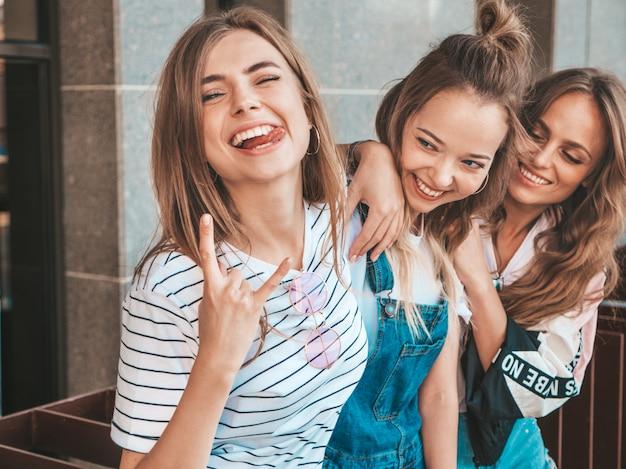 Ritratto di tre giovani belle ragazze sorridenti hipster in abiti estivi alla moda. donne spensierate sexy che posano per strada. divertimento dei modelli positivi. mostrano la lingua e il segno del rock and roll