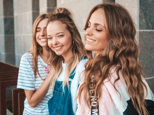 Ritratto di tre giovani belle ragazze sorridenti hipster in abiti estivi alla moda. donne spensierate sexy che posano per strada. divertimento dei modelli positivi
