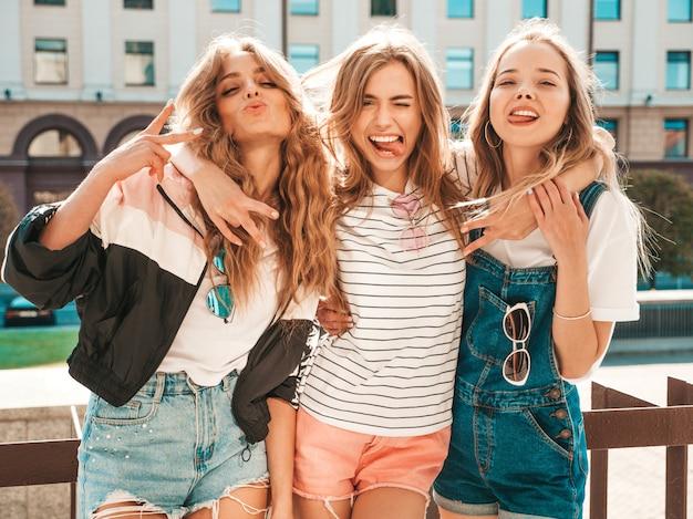 Ritratto di tre giovani belle ragazze sorridenti hipster in abiti estivi alla moda. donne spensierate sexy che posano per strada. divertimento di modelle positive. lingua di mostra